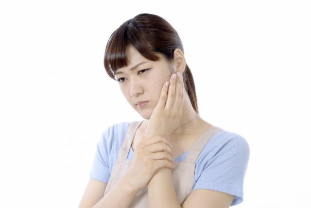 顎関節症でつらそうにしている女性