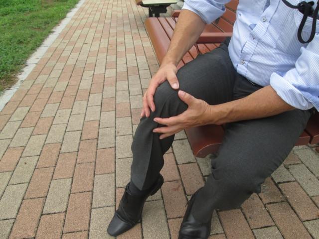 膝の痛みでつらそうにしている男性